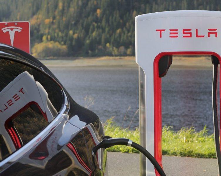 Ein Elektroauto der Marke Tesla lädt an einer Ladesäule.