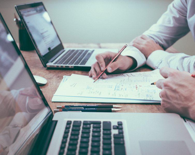 Zwei Personen sitzen vor Laptops und schreiben etwas auf ein Papier. Bei New Work könnten die Menschen zukünftig öfter im Homeoffice arbeiten.