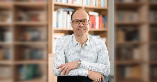 Prof. Dr. Christoph Bieber, Universität Duisburg-Essen. Foto: Prof. Christoph Bieber Background: Photo by Pickawood on Unsplash